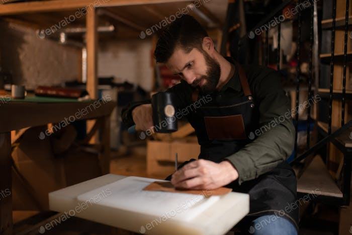 Bearded craftsman making leather handicraft in cozy studio