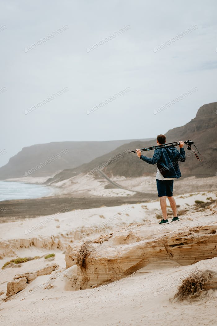Photographer with camera looking for motive of unique landscape. Sand dunes and volcanic cliffs on