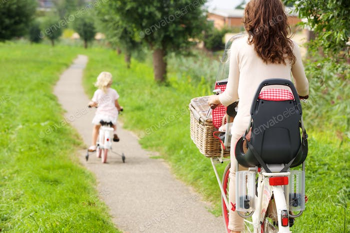 Woman and little girl riding bikes in park