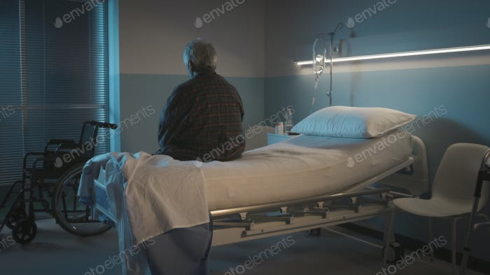 Depressed senior sitting on the hospital bed alone