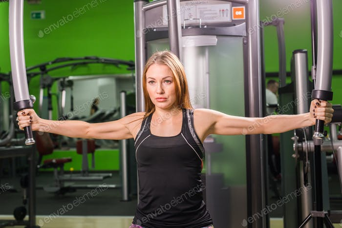 young fitness woman execute exercise with exercise-machine in gym