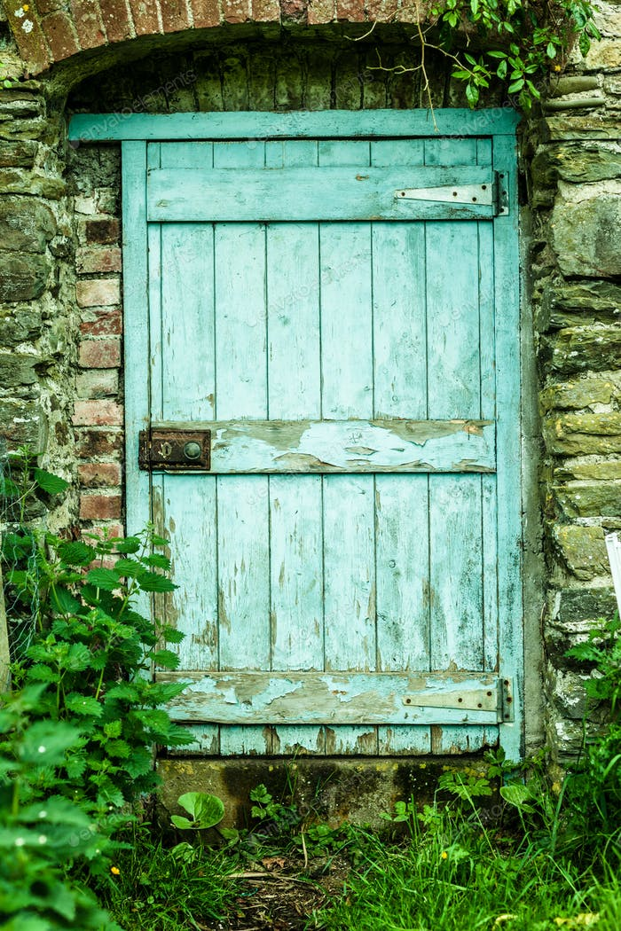 Blue rustic wooden door in a stone wall in the countryside