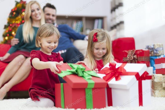 Süße kleine Mädchen öffnen Weihnachtsgeschenke