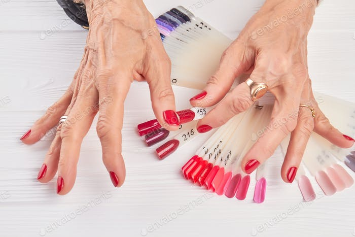 Old woman compares nail color with nail sample