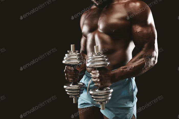 Strong athletic body of black bodybuilder holding dumbbells