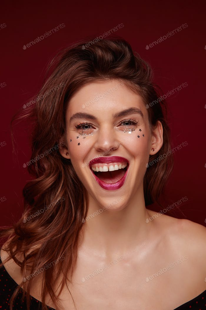 Joyful young attractive brown haired woman with makeup smiling broadly with wide mouth opened