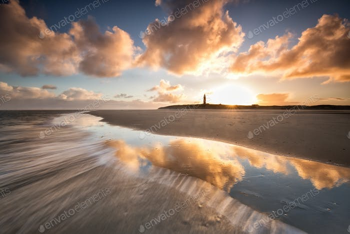 dramatic sunrise over North sea coast with lighthouse