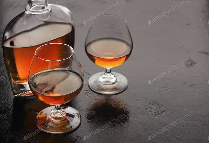 Two glasses of brandy or cognac and bottle on black