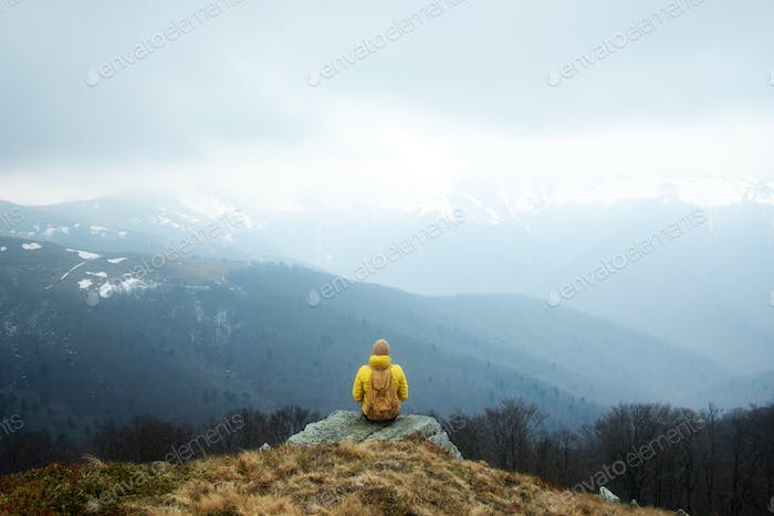 Man with backpack in spring mountains