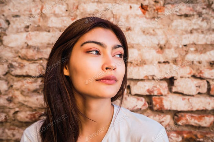 Young latin woman against brick wall.