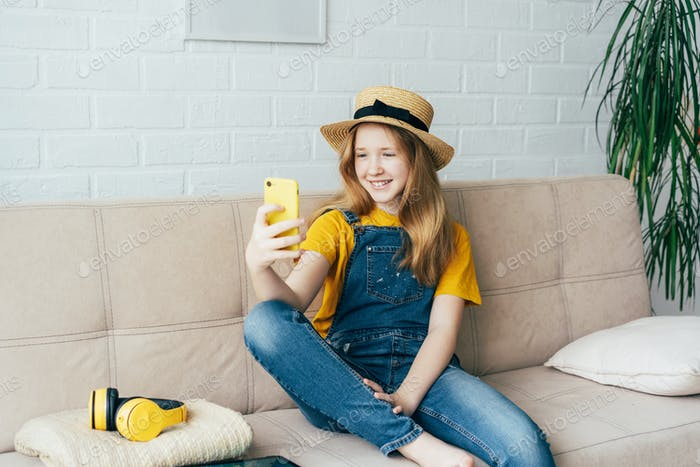 Cheerful redhead girl in a straw hat and denim overalls posing and taking a selfie on a smartphone.