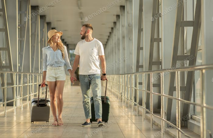Happy tourists walking in airport with luggage