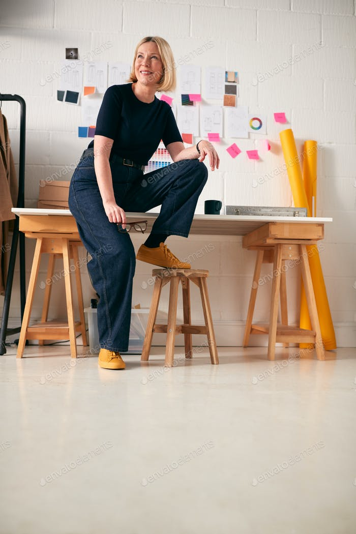 Portrait Of Confident Mature Businesswoman Sitting On Desk In Start Up Fashion Business