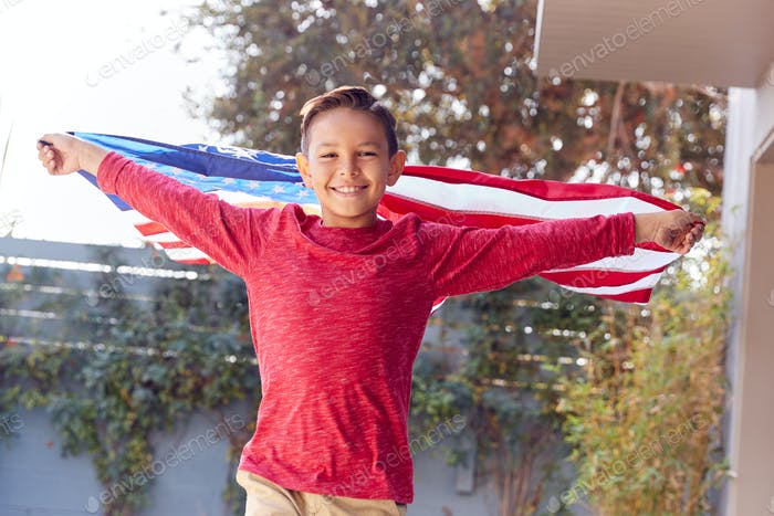 Portrait Of Proud Hispanic Boy Wrapped In Stars And Stripes American Flag Running Towards Camera