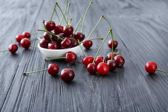 Fresh cherries closeup with green leaves on blue rustic wood