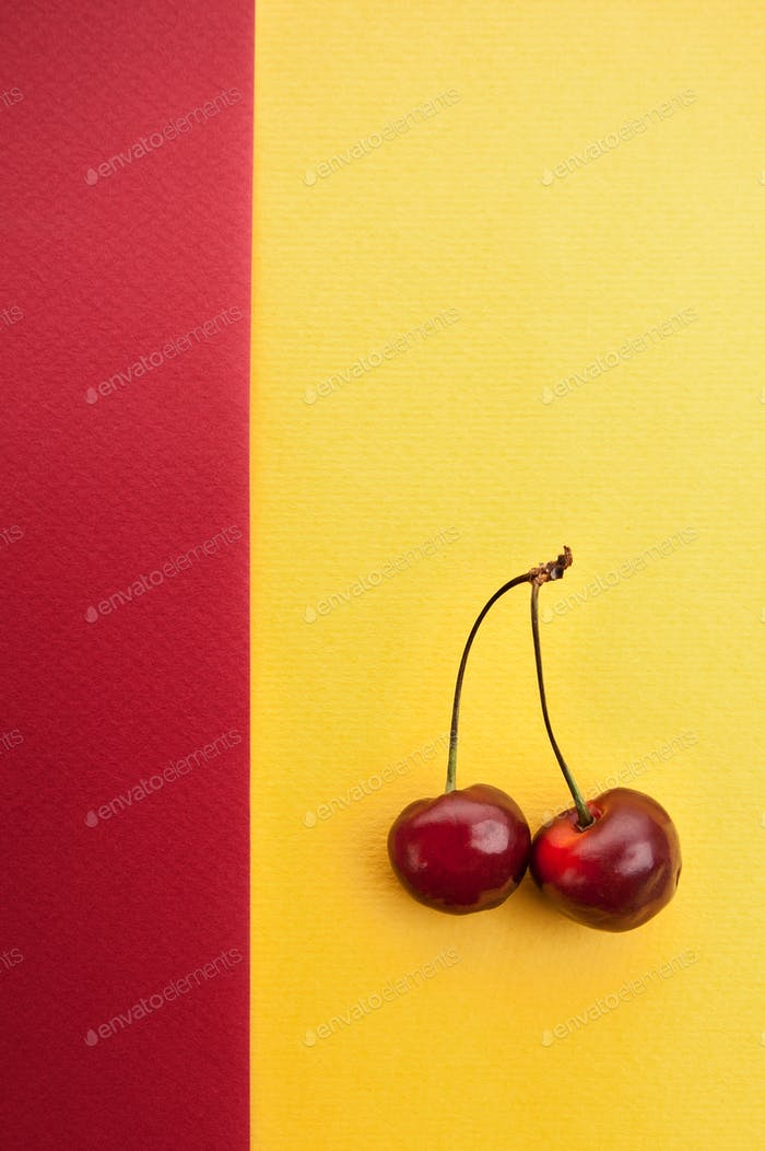 Kirsche auf einem rot-gelben strukturierten Hintergrund mit einem Platz für Ihre