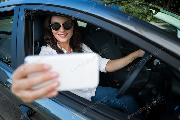 Woman taking selfie with mobile phone in car