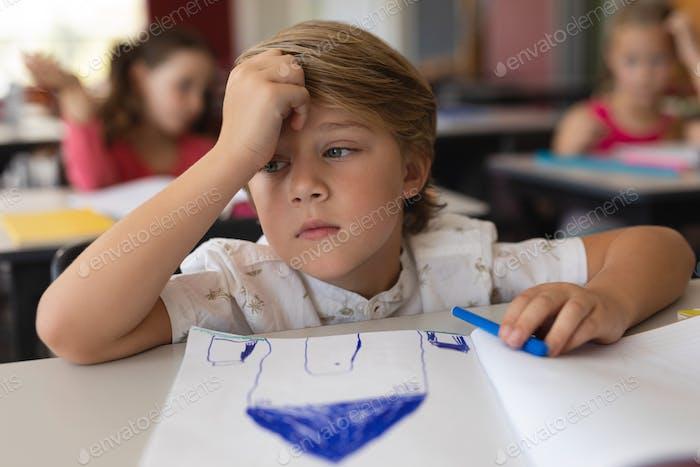 Sad schoolboy studying in classroom sitting at desks in school