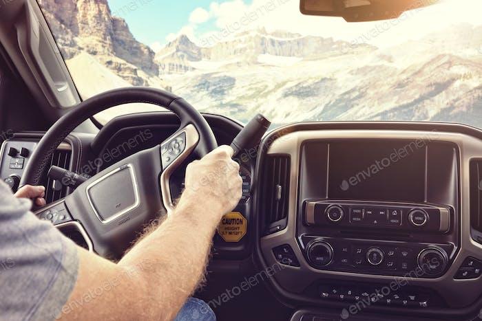 Fahren Sie ein Auto oder LKW auf einer ländlichen Straße durch die Berge