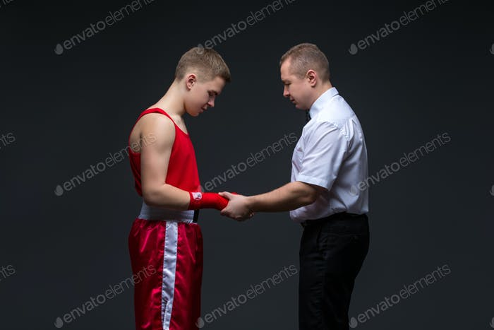 Referee checking young boxer