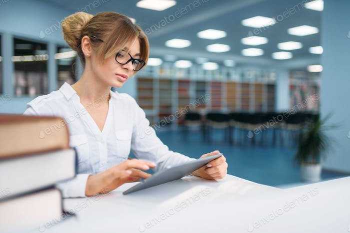 Pretty female student sitting in library