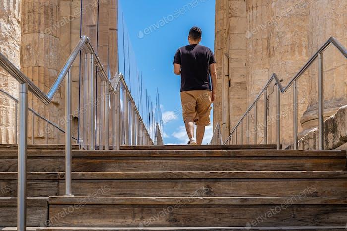 Athen Griechenland. Junger Mann verlassen Akropolis, Holztreppen und covid 19 Schutzmaßnahmen