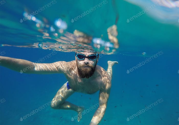 Man doing underwater selfie shot with selfie stick