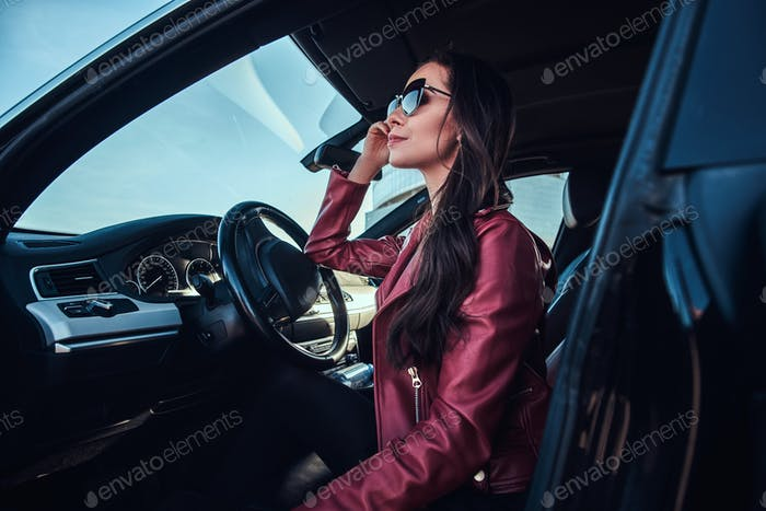 Attractive pensive woman in red jacket and sunglasses is posing in her car