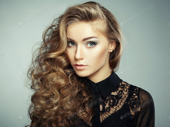 Portrait of beautiful young blonde girl in black dress. Fashion