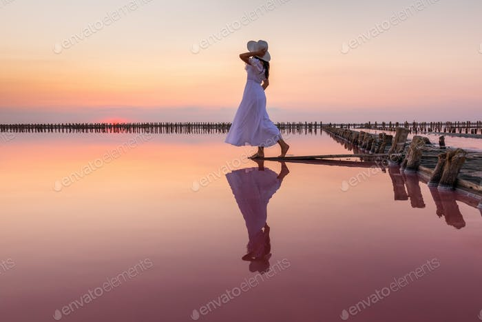 Woman in a white dress at sunset on a pink salt lake