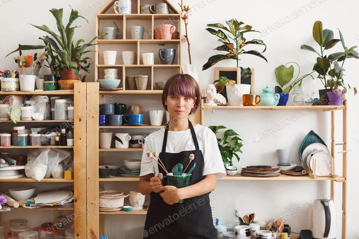 Beautiful girl with colorful hair in black apron and white T-shirt holding handmade bowl