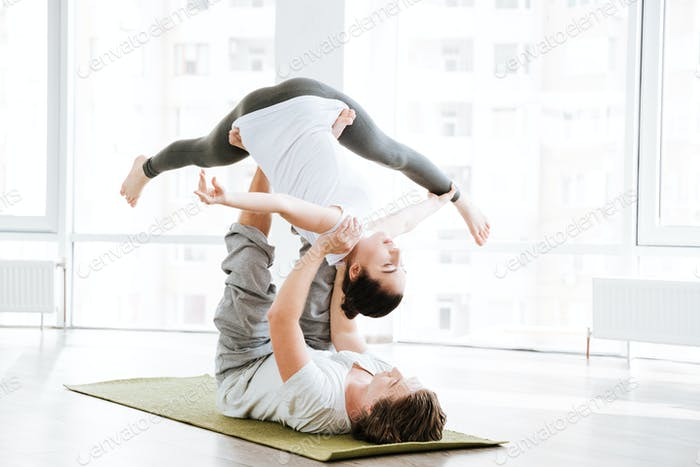 Couple doing flexibility workout in yoga studio