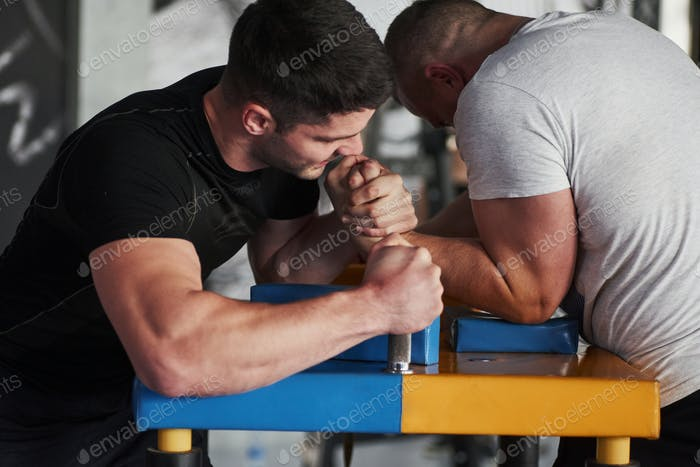 Muscular guys trying to win. Arm wrestling challenge between two men. Match on a special table