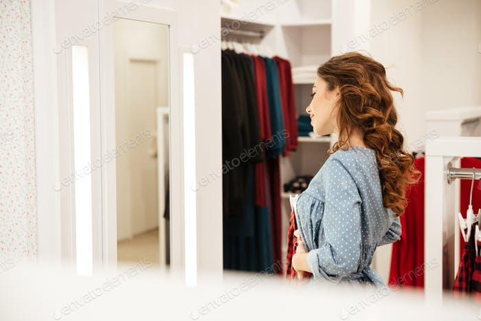 Smiling woman shopper in blue dress choosing clothes