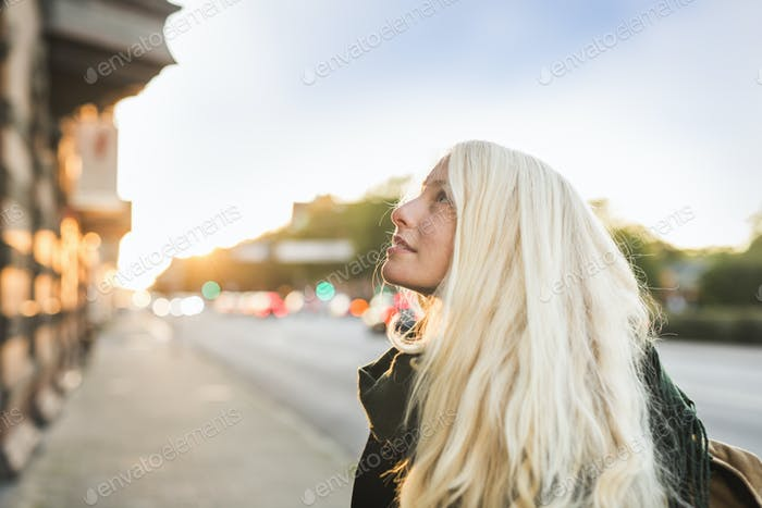 Close-up of teenage girl looking up at street