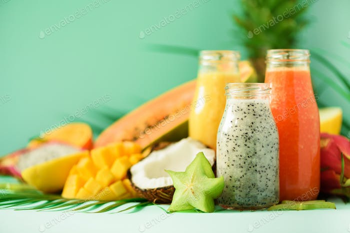 Papaya, dragon fruit, pineapple, mango smoothie in jars on turquoise background. Detox, vegan diet