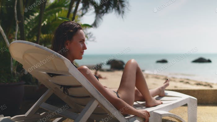 Relaxed Woman Lying on Sunbed by Ocean Tanning