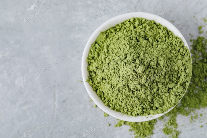 Green matcha tea powder in white bowl