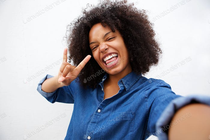 Selfie portrait of happy woman making rock and roll hand gesture