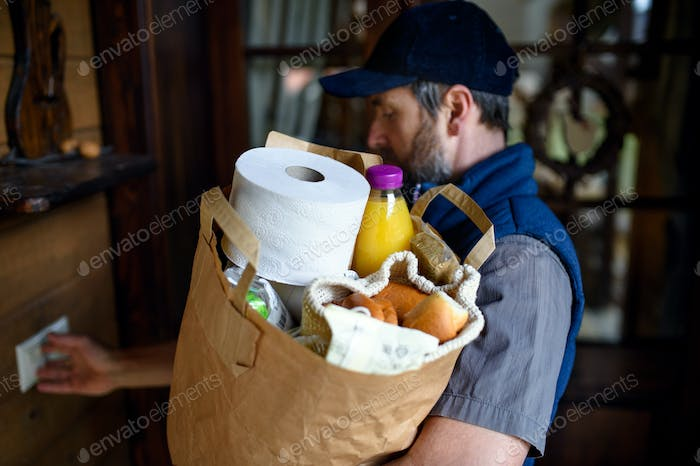 Man courier delivering shopping, knocking on the door