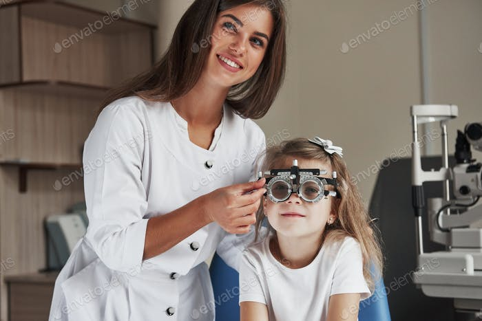 Gorgeous female ophthalmologist smiling when doing her job in cabinet with little girl