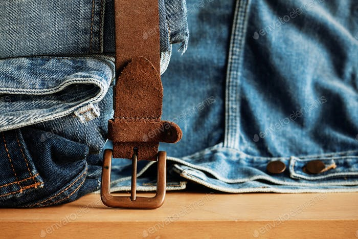 Old belt and jeans on wooden