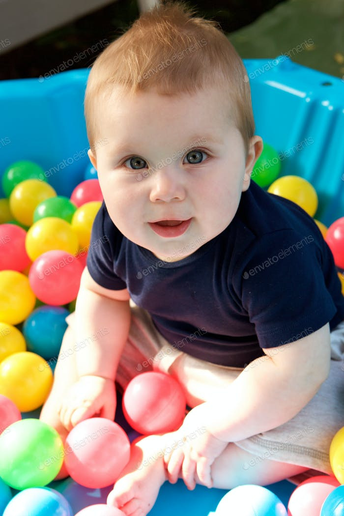 cute little baby boy having fun in ball pit