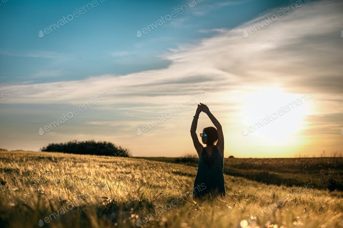 Happy woman enjoying the life in the golden field