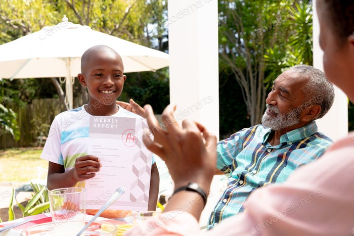African American boy showing his grandfather his homework during a family lunch in the garden
