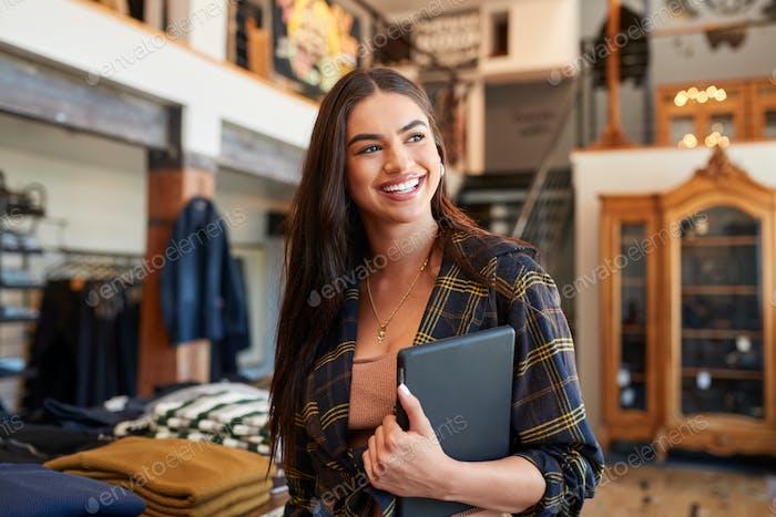 Lächelnd Weibliche Besitzer von Modegeschäft Stehen Vor Kleidung Display