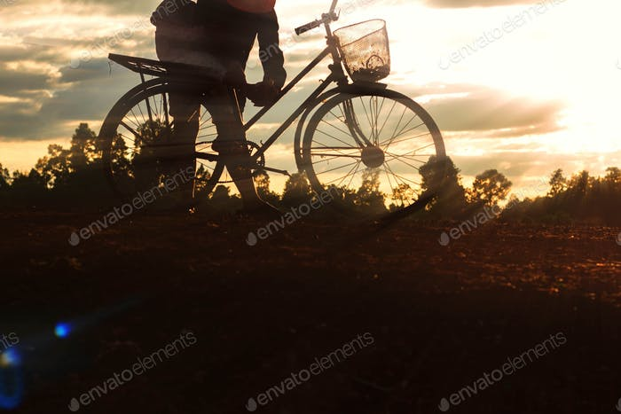Farmer and bicycle at the sunset