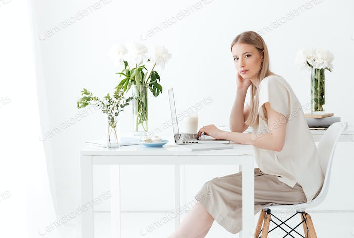 Serious woman sitting indoors using laptop