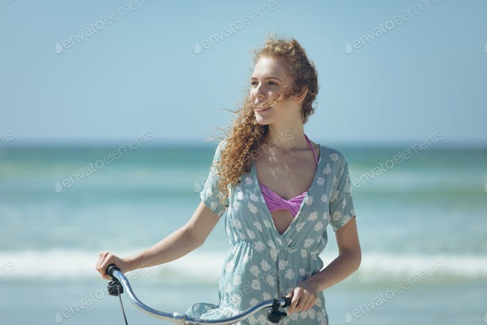 Woman holding bicycle at beach