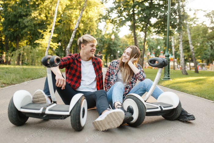 Young couple sitting on road with gyro board